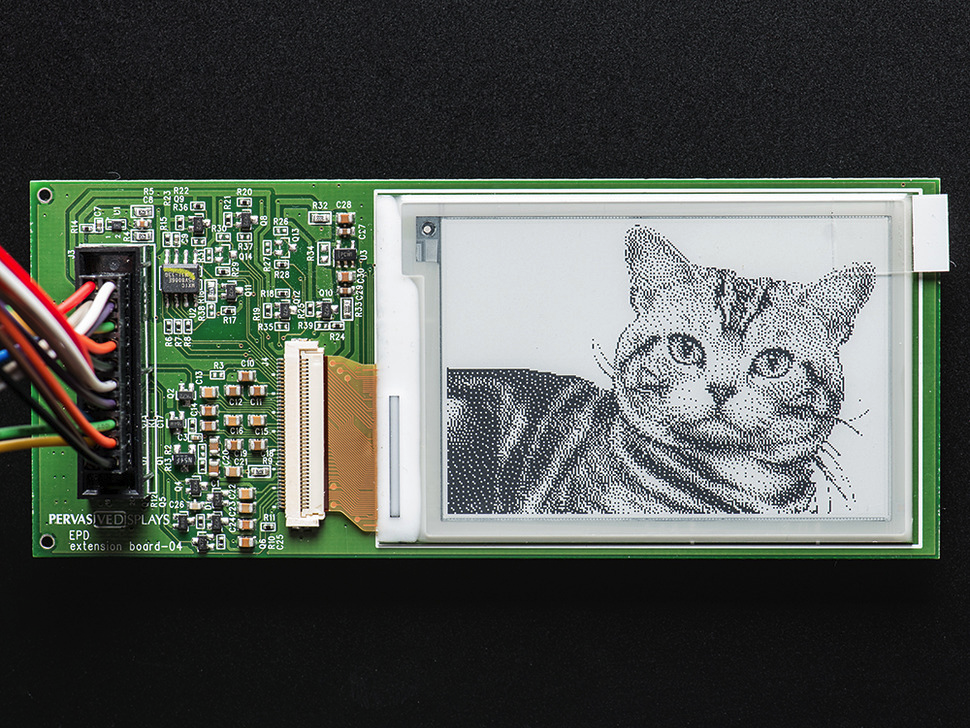 an e-ink display on a circuit board with the image of a cat on it